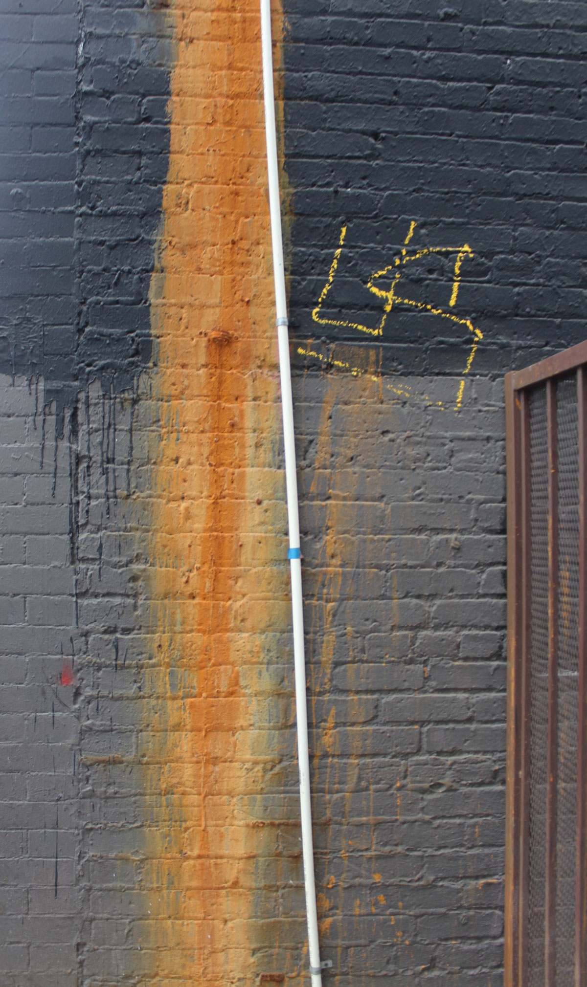 black and grey wall with orange rust due to a water leak and yellow graffiti lettering
