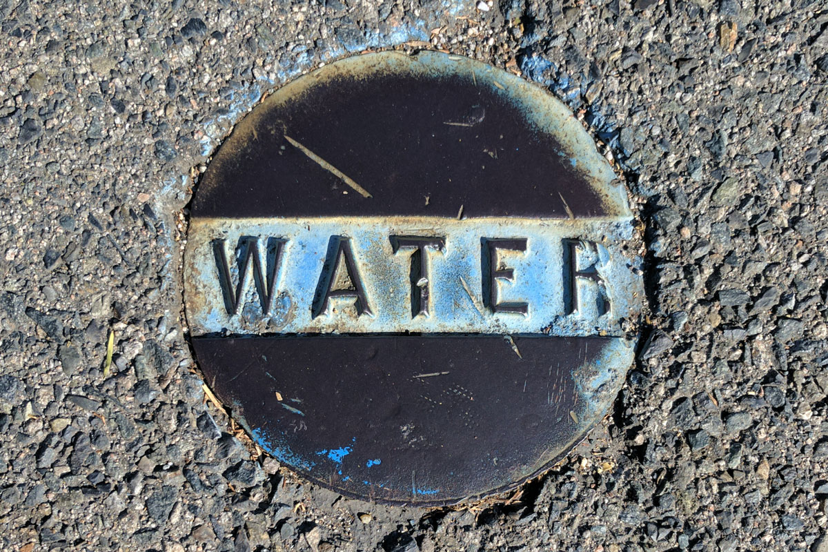 Water cover in the street that has a blue background behind the text that says water